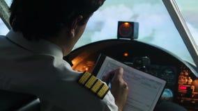 Kapitein die vluchtplan, vliegtuig invullen die op automatische pilootwijze vliegen, proef op het werk stock footage