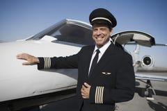Kapitein Standing By Aircraft bij Vliegveld Stock Afbeeldingen