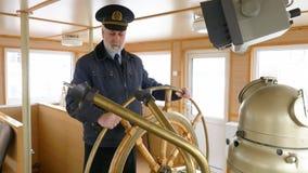 Kapitein van het schip bij het roer in de stuurhut stock footage