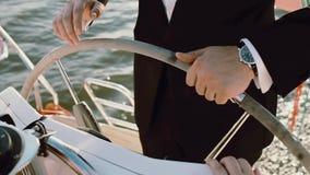 Kapitein van het schip die zich achter stuurwiel bevinden Jonge zakenman die het jacht in heldere zonnige dag drijven stock video