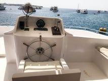 Kapiteins` s cabine op een schip, een boot, een cruisevoering met een stuurwiel, een dashboard, een leunstoel, een mariene kompas Royalty-vrije Stock Foto