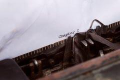 kapitel ett som är skriftligt på en skrivmaskin royaltyfri fotografi