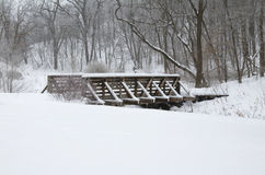 Kaposia Park Snow Covered Bridge. Photo of Kaposia Park after snowfall showing pedestrian wooden bridge and trusses covered in fresh snow with forest in royalty free stock images