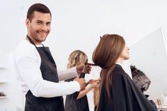 Kapper die bruin haar van mooie vrouw krullen Vrouwenzorg over kapsel royalty-vrije stock afbeelding