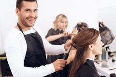 Kapper die bruin haar van mooie vrouw krullen Vrouwenzorg over kapsel stock foto