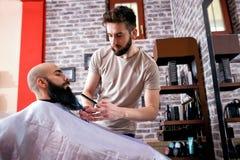 Kapper die een cliënt` s baard met schaar snijden stock afbeeldingen