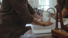 Kapper die een handdoek in gootsteen doorweken stock video