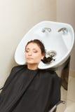 Kapper die haar haar van de vrouwenklant wassen Stock Foto's