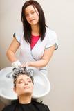 Kapper die haar haar van de vrouwenklant wassen Stock Fotografie