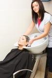 Kapper die haar haar van de vrouwenklant wassen Royalty-vrije Stock Foto's