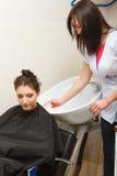 Kapper die haar haar van de vrouwenklant wassen Stock Afbeelding