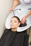 Kapper die haar haar van de vrouwenklant wassen Royalty-vrije Stock Foto