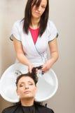 Kapper die haar haar van de vrouwenklant wassen Stock Foto