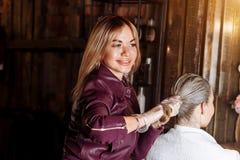 Kapper die haar van klant na het toepassen van het masker trekken Sterk en gezond haar Kuuroord, haarklei, haarverzorging stock foto