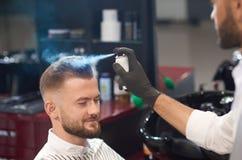 Kapper die haar van mannetje met nevel in kapperswinkel vastzetten royalty-vrije stock fotografie