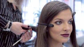 Kapper die haarkrulspelden toepassen op close-up van het kapsel het jonge mooie meisje stock video