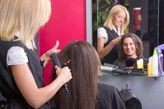Kapper die het haar van de vrouw in schoonheidssalon rechtmaken Royalty-vrije Stock Afbeeldingen
