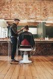 Kapper die kapsel geven aan cliënt bij salon royalty-vrije stock afbeelding