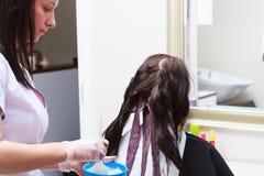 Kapper die kleuren vrouwelijke klant toepassen bij salon, die haarverf doen stock afbeeldingen