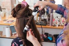 Kapper die krullend ijzer voor haar van wijfje met smartphone gebruiken stock foto's