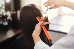 Kapper die lang bruin haar met schaar in orde maken royalty-vrije stock foto's