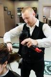 Kapper die lang zwart haar met droogkap en ronde borstel drogen royalty-vrije stock afbeeldingen
