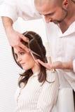Kapper die met schaar bij salon wordt gesneden stock afbeelding