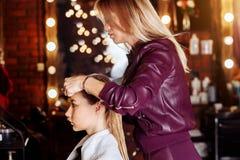 Kapper die nat haar van mooie jonge blonde vrouw in schoonheidssalon borstelen na het wassen van haar Haargezondheid, schoonheids royalty-vrije stock foto
