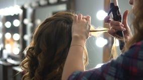 Kapper die omslag doen die bruin haar in een schoonheidssalon krullen met ijzer stock video