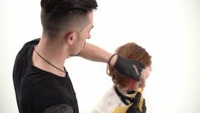 Kapper een kam en een schaar die perfoming een kapsel voor een gembercliënt houden stock footage