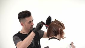 Kapper een kam en een schaar die perfoming een kapsel voor een gembercliënt houden stock video