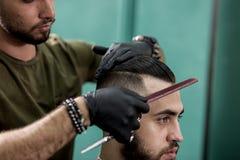 Kapper in het zwarte haar van handschoenenkammen van de modieuze mens bij een herenkapper royalty-vrije stock afbeelding