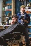 Kapper met de hairdryerwerken aangaande kapsel voor de gebaarde achtergrond van de mensenherenkapper Hipster gebaarde cli?nt die  royalty-vrije stock afbeelding