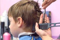 Kapper scherpe haren met schaar op het hoofd van de jongen Achtermening, de handenclose-up van de stilist stock afbeelding