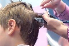 Kapper scherpe haren met schaar op het hoofd van de jongen Achtermening, de handenclose-up van de stilist royalty-vrije stock foto's