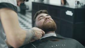 Kappers in orde makende baard met scheerapparaat stock video