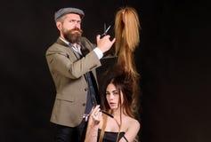 Kappersschaar De kapper maakt tot kapsel een vrouw met lang haar De hoofdkapper doet kapsel en stijl met royalty-vrije stock fotografie