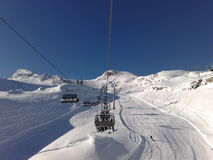 Kaprun. Snowboarders on chair lift,blue sky ,powder Royalty Free Stock Images