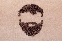 Kapsel en baard van koffiebonen wordt gemaakt op triplex in centrum dat royalty-vrije stock foto