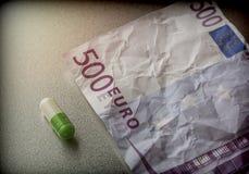 Kapsel von weißem und von Grünem auf einer Karte benutzte 500 Euros, Lizenzfreie Stockfotos