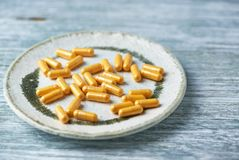 Kapslar för Coenzyme Q10 dietary supplements lantligt trä för bakgrund arkivbild