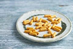 Kapslar för Coenzyme Q10 dietary supplements lantligt trä för bakgrund arkivfoto