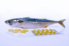 Kapslar för fiskolja och fiskmakrill (på vit bakgrund) Arkivbilder