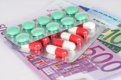 Kapslar och preventivpillerar i blåsa med eurosedlar Fotografering för Bildbyråer