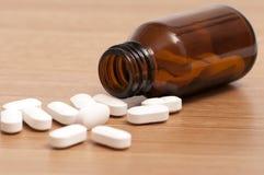 Kapslar och preventivpillerar i en flaska arkivfoton
