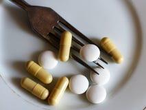 Kapslar och preventivpillerar på plattan med gaffeln, bantar och viktförlust Arkivbild