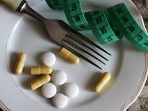 Kapslar och preventivpillerar på plattan med gaffeln, bantar och viktförlust, bandet Arkivfoto