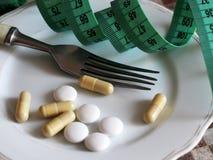 Kapslar och preventivpillerar på plattan med gaffeln, bantar och viktförlust, bandet Arkivfoton