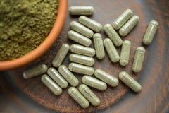 Kapslar och pulver för tilläggkratomgräsplan på den bruna plattan ört arkivfoton