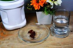 4 kapsuł dodatkowy jedzenie i szkło woda na stole Fotografia Royalty Free